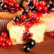 Tasty muffins with berries on wooden table — Stock Photo #29997505
