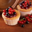 Tasty muffins with berries on wooden background — Stock Photo #29998073