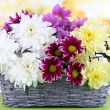 Bouquet of beautiful chrysanthemums in wicker basket on table on bright background — Stock Photo #29998141