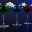 Alcoholic cocktails in martini glasses on dark blue background — Stock Photo