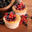Tasty muffins with berries on wooden table — Stock Photo #29998247