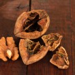 Broken walnut on wooden table — Stock Photo