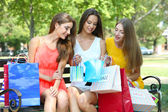 Three beautiful young woman with shopping bags in park — Foto de Stock
