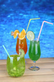 Tasty cocktails on swimming pool background — Stock Photo
