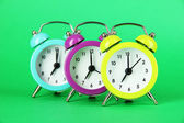 Colorful alarm clock on green background — Stok fotoğraf