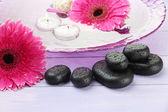 Spa-steine, schöne gerbera blumen und kerzen auf dem wasser — Stockfoto