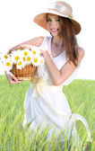 Portrait of beautiful young woman with flowers in the field — Stock Photo
