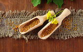 Mustard seeds with mustard flower on wooden background — Stock Photo