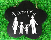 Family from paper on wooden board on bright background — Stock Photo