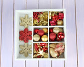 Wooden box filled with christmas decorations, on color wooden background — Stock Photo