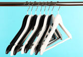 Black and white clothes hangers on color background — Stockfoto