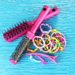 Scrunchies, hairbrush and hair - clip on blue background — Stock Photo #30007839