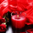 Stock Photo: Beautiful romantic red candle with flowers and silk cloth, close up