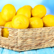 Ripe lemons in wicker basket on table on bright background — Stock Photo #30009909