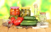 Sabrosos verdes pepinos y tomates rojos en cesta, en mesa de madera sobre fondo brillante — Foto de Stock