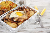 Food in boxes of foil on wooden table — Stock Photo