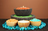 Candle in stone bowl with marine salt, on bamboo mat, on brown background — Stock Photo