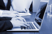 Female hands with digital tablet on office background in shades of grey — Stock Photo