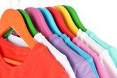 Verschillende shirts op kleurrijke hangers op witte achtergrond — Stockfoto