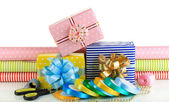 Materials and accessories for wrapping gifts with holiday gifts isolated on white — Stock Photo