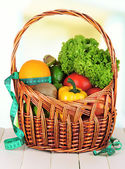 Fresh vegetables in wicker basket on table on light background — Stock Photo