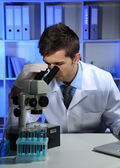 Young laboratory scientist looking at microscope in lab — Stock Photo