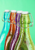 Colorful bottles on green background — Stock Photo