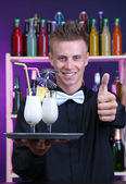Portrait of handsome barman with Pina colada cocktail, at bar — Stock Photo