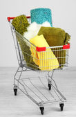 Shopping cart with colorful carpets and plaids, on color wall background — Stock Photo