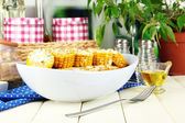 Flavored boiled corn on plate on wooden table on window background — Stock Photo