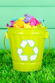 Recycling bin on green grass on color wooden background — Stok fotoğraf