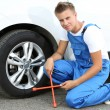 Auto mechanic changing wheel — Stock Photo #30047535