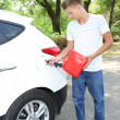 Man pouring fuel into gas tank of his car from red gas canister — Stock Photo
