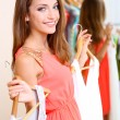 Beautiful girl with dresses near mirror — Stock Photo