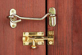 Metal hook and deadbolt in wooden door close-up — Stock Photo