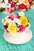 Hermoso ramo de flores en florero de color, sobre fondo brillante — Foto de Stock