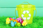 Recycling bin on green grass on color wooden background — Stock Photo