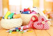 плетеные корзины с аксессуарами для рукоделия на деревянном столе, на светлом фоне — Стоковое фото