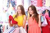 Two beautiful young woman in shop with shopping bags — Стоковое фото