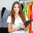 Beautiful young stylist near rack with hangers — Stock Photo #30051307