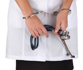 Doctor with stethoscope in handcuffs isolated on white — Stok fotoğraf