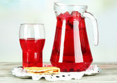 Pitcher and glass of compote on napkin on wooden table on light background — Stock Photo