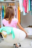 Piękna dziewczyna wybiera ubrania na wieszakach w pokoju — Zdjęcie stockowe