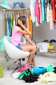 Beautiful girl chooses clothes in room — Stok fotoğraf