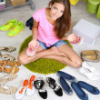 Beautiful girl chooses shoes in room — Foto de Stock