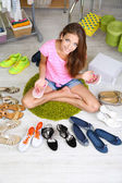 Beautiful girl chooses shoes in room — Stock Photo