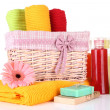 Colorful towels in basket, cosmetics bottles and soap, isolated on white — Stock Photo