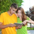 Two happy young students with laptop in park — Stock Photo #30111047