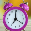 Alarm clock on table on bright background — Stock Photo #30117603