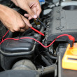 Auto mechanic uses multimeter voltmeter to check voltage level in car battery — Stock Photo #30117923